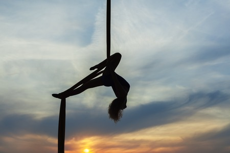 Womans equilibrist does tricks high in the sky in the setting sun. Only the contours of the athlete.