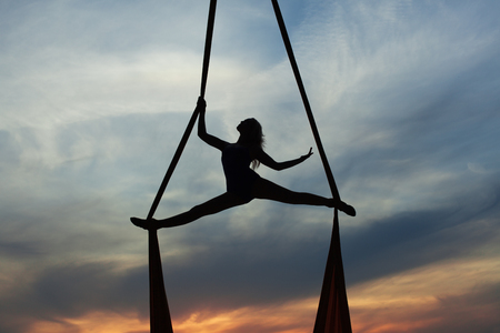 Sport exercises with aerial silk outdoor, sky background.