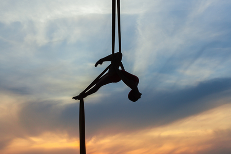 Woman in a hammock does tricks against the sky, she is an athlete aerial acrobat.