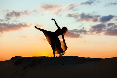 flit: Woman dances at sunrise in the sun. The backlight of the sun only contours of the figures are visible. Stock Photo