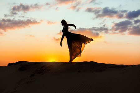 flit: Female dancer dances at sunset, her dress is fluttering and translucent. The backlight of the sun only contours of the figures are visible. Stock Photo
