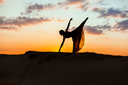 flit: Woman beautifully dances in the rays of the evening sun. The backlight of the sun only contours of the figures are visible.
