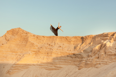 flit: Woman dances high on a sand dune against the sky.