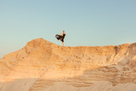 flit: Woman runs down the slope of a sand dune, she is high against the sky.