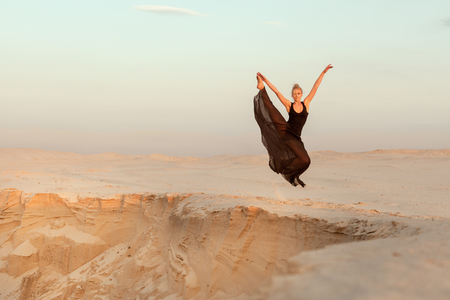 Woman in dance flies over an abyss in the desert.