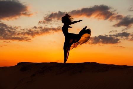 flit: Woman runs along the barkhans against the backdrop of the setting sun. Stock Photo