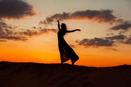 flit: Female figure against the backdrop of the setting sun.