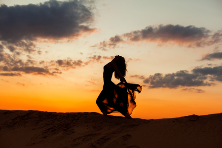 flit: Female figure during a dance against the backdrop of the setting sun. Stock Photo