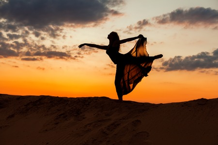 flit: Dancing woman figure on the background of the setting sun. Stock Photo