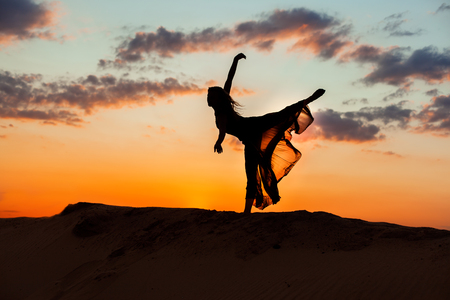 flit: Dancing at night in the sand against the backdrop of the setting sun, the silhouette of a dancer.