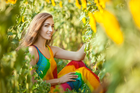 fruition: Lovely woman among yellow sunflowers in the field.