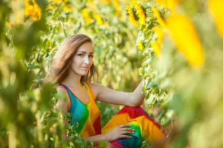 fruition: Pretty woman smiling while sitting in tall grass.