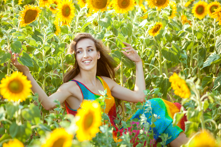 Happy and lovely woman sits in a field among yellow sunflowers. Stock Photo
