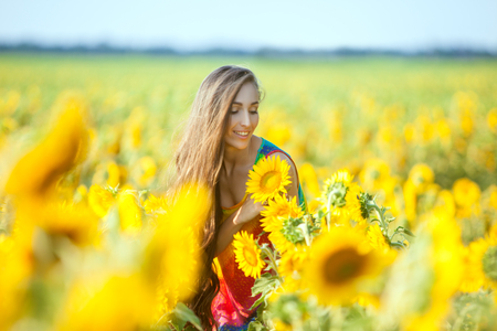 The woman on the field with yellow flowers, she is happy.