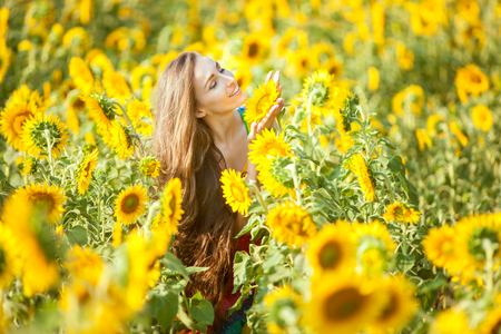fruition: Happy woman on a flower field enjoys herself. Stock Photo