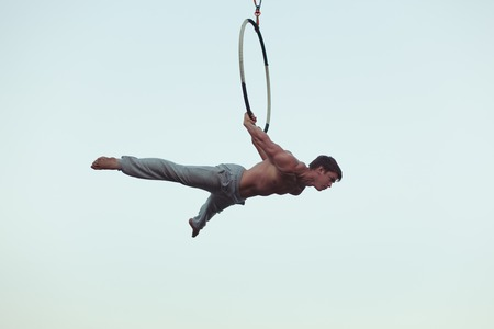 Man is an acrobat high in the sky, he shows the performance on the ring. Stock Photo