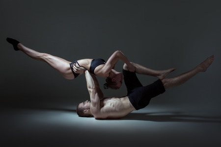 Athletes gymnasts demonstrate power tricks, they have beautiful muscular bodies. Фото со стока