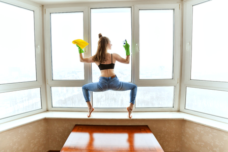 Woman washes windows in a yoga pose, she is doing sports while cleaning an apartment. Stock Photo