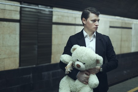Young man with a teddy bear, he worries before the meeting.