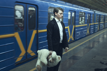 Sad man with a teddy bear in his hands standing in a subway station near train.