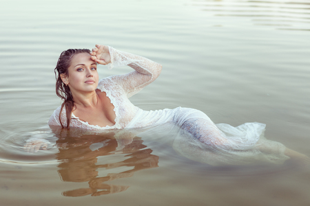 Wet woman lies in the water, she relaxes. Stock Photo