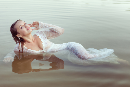 Portrait of a beautiful young woman in a white dress. She lies in the water on the river bank.