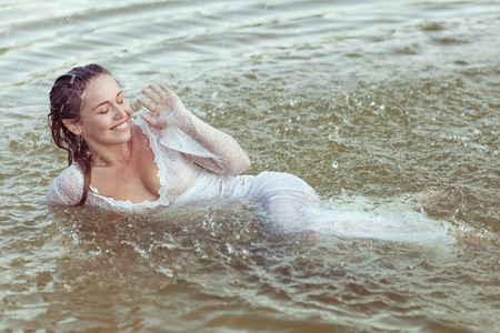 Beautiful young woman lies in the water. She closed her eyes from the splashes of water and laughed. Stock fotó