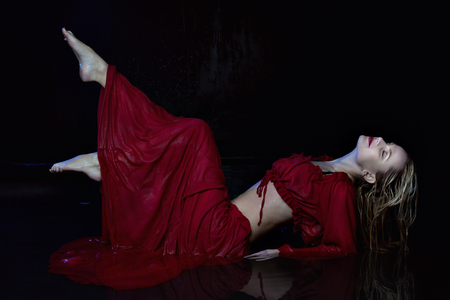 Wet woman in a red dress is lying in the water.