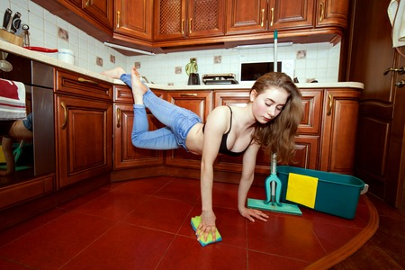 Young athletic woman is cleaning the apartment, she washes the floors.