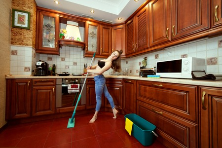 Woman washes the floor with a mop and dances.