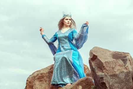 Beautiful elf woman in blue dress sits on a stone.
