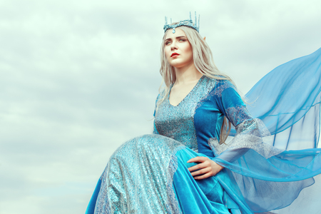 Portrait of a beautiful young woman elf in a blue dress.