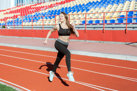 Young beautiful woman is engaged in the stadium. She is running.