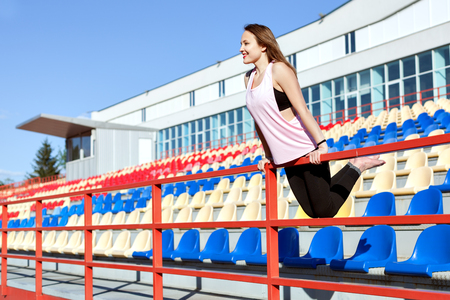 Young woman in sportswear standing on the stadium podium. Stock fotó