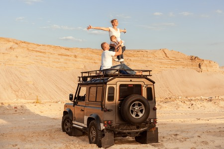 Young family with child on the roof of a car in the desert.