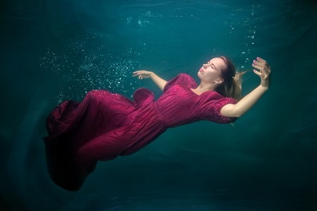 Woman in a red dress is underwater, she is sleeping. Stock Photo