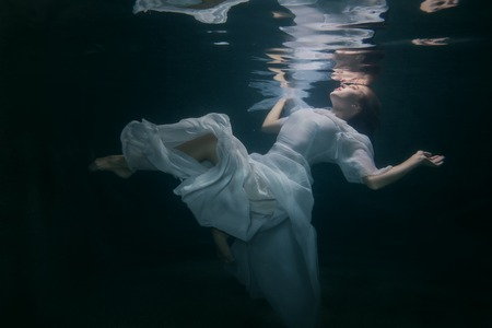 Beautiful woman in a white dress swims under the water.