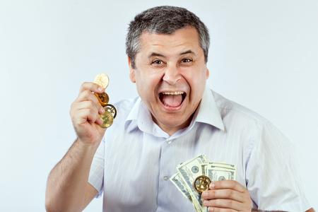El hombre grita de alegría cuando tiene bitcoins y dólares en sus manos.