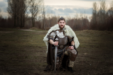 Knight in armor with a sword in hand, standing on one knee. Stock Photo