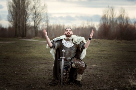 Knight raised his hands to the sky in pleading, wearing a chain mail. Stock Photo