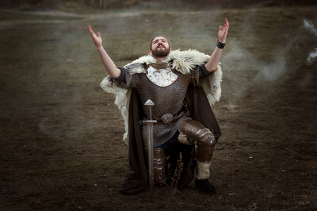 Knight in armor knelt down and pray raised his head to heaven. Stock Photo
