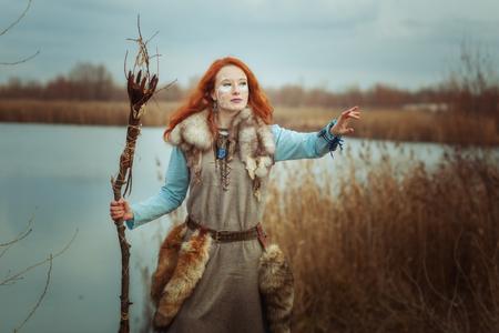 Die heidnische Frau ist eine Schamanin mit einem Stab in der Hand.