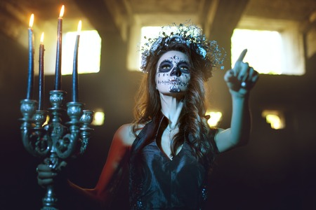 Young woman with make up for the celebration of Halloween holding a candlestick with burning candles. Stok Fotoğraf
