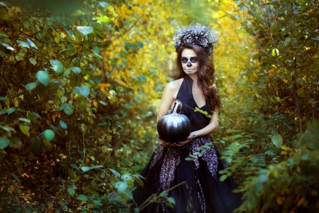 Portrait of a young woman with makeup for Halloween. She is standing in the forest and holding a black pumpkin.