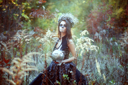 Young woman with Halloween make-up in fairytale forest with pumpkin.