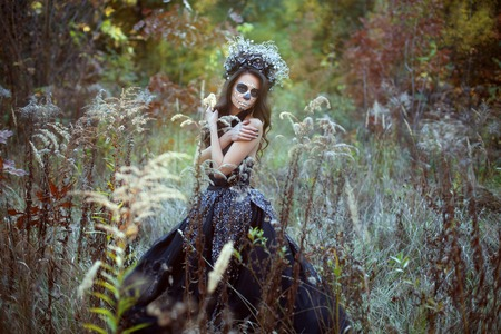 Portrait of a young woman with make-up for Halloween in a fairy forest.