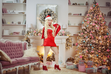 Beautiful woman in a red dress standing near the New Year tree.