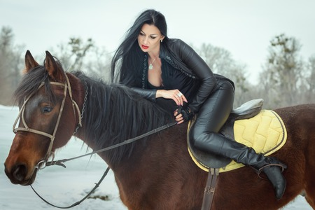 Portrait of a beautiful brunette woman, she sits on horseback.