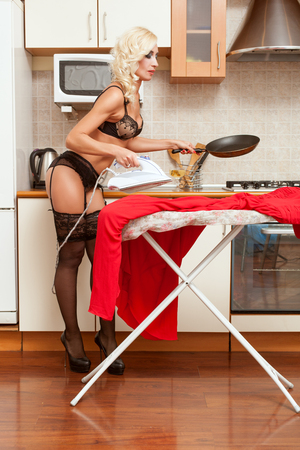 Woman irones her clothes and cooks food at the same time. 免版税图像