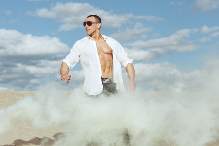 Young man in a white shirt stands among the smoke in the desert. Hi holds cigar.